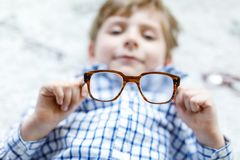 Close-up portrait of little blond kid boy with brown eyeglasses Stock Images