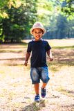 Close up portrait of little boy running outdoors in park stock photo