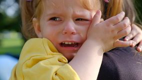 Close-up portrait of a little charming girl crying in her mother arms stock video footage