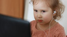 A little cute girl in headphones looks at the screen monitor computer. Funny child looking tv, video,cartoon or playing. Close-up portrait a little cute girl in stock footage