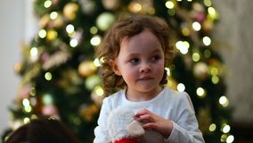 Close-up portrait of a little girl with the Christmas tree as the background. stock video