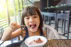 Close-up portrait of a little girl having breakfast on table Royalty Free Stock Photos