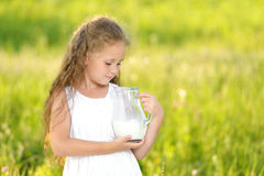 Close up portrait little girl holding pitcher of milk outdoor summer. Close up portrait little girl holding pitcher of milk outdoor. Curly kid having breakfast Stock Images