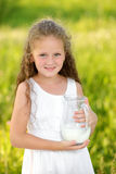 Close up portrait little girl holding pitcher of milk outdoor summer. Close up portrait little girl holding pitcher of milk outdoor. Curly kid having breakfast Royalty Free Stock Photos