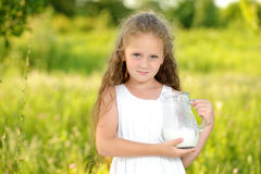 Close up portrait little girl holding pitcher of milk outdoor summer. Close up portrait little girl holding pitcher of milk outdoor. Curly kid having breakfast Royalty Free Stock Images