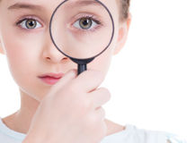 Close-up portrait of  little girl looking through a magnifying g. Close-up portrait of cute little girl looking through a magnifying glass - isolated on white Stock Photos