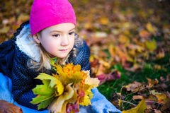 Close up portrait of little girl with maple leaves lying in autu Stock Images