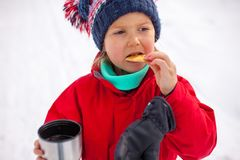 Close-up portrait of little girl in red winter jacket drincking tea from the thermos cup with biscuit royalty free stock image