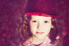 Close up portrait of a little girl in shiny red hat. Instagram f Stock Photo