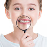 Close-up portrait of little girl showing teeth through a magnify Stock Photography