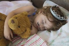 Close-up portrait little girl sleeping in bed. girl with a crown of princess on her head in bed hugging a teddy bear toy Stock Photos