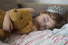 Close-up portrait little girl sleeping in bed. girl with a crown of princess on her head in bed hugging a teddy bear toy Stock Image