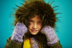 Close up portrait of little girl in warm autumn jacket with fur hood in green and mittens, shot on blue royalty free stock photography