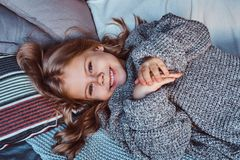 Close-up portrait of a little girl in warm sweater lying on bed. stock images