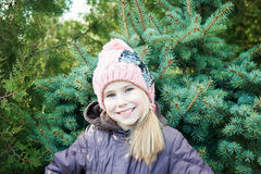 Close up portrait  little girl, winter time  spruce on background Royalty Free Stock Image