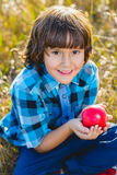 Close up portrait little handsome boy biting off piece of apple outside Stock Photo