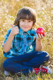 Close up portrait little handsome boy biting off piece of apple outside Royalty Free Stock Photo
