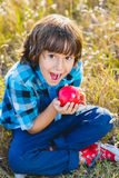 Close up portrait little handsome boy biting off piece of apple outside Stock Image