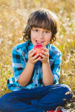 Close up portrait little handsome boy biting off piece of apple outside Royalty Free Stock Image