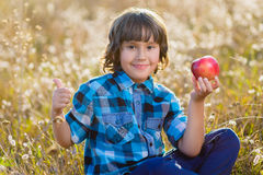 Close up portrait little handsome boy biting off piece of apple outside Stock Photography