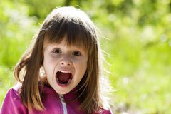 Close-up portrait of a little pretty girl with shouting face exp Royalty Free Stock Image