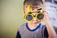 Close up Portrait of a little smiling boy in a funny sun glasses stock photos