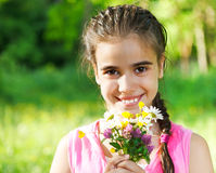 Close up portrait of little smiling girl with spring flowers. Bouquet Stock Images
