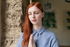 Close-up portrait of long-haired redhead woman posing for a portrait with closed eyes and folded hands stock photo