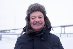 Close up portrait of lovely smiling grandpa. With mustache. Grandfather in snowy outdoors wearing warm hat royalty free stock photo