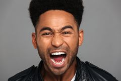 Close up portrait of a mad african man with stubble. Dressed in leather jacket looking at camera and screaming isolated over gray background Royalty Free Stock Photography