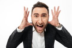 Close up portrait of a mad young bearded man. Looking at camera and shouting isolated over white background Stock Photography