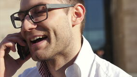 Close up portrait of male businessman on smart phone outdoors in white shirt. Close up of a young man talking on a mobile phone near his office. Young urban stock footage