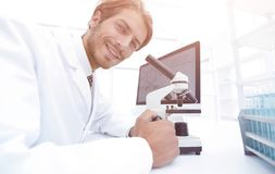 Student in biology using microscope in training class. Close-up portrait of a male scientific researcher using microscope in the laboratory Stock Image