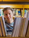 Close up portrait of a male student in the library. Close up portrait of a young male student amid bookshelves in the college library Royalty Free Stock Photo