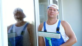 Close-up, portrait of a male worker of cleaning service, in blue overalls and in a cap, blaser, with a special mop for stock video