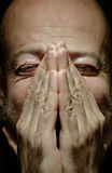 Close-up portrait of a man with closed eye and folded hands Stock Images