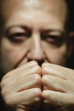 Close-up portrait of a man with closed eye and folded hands Royalty Free Stock Photo