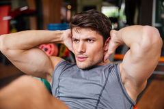 Close up portrait of man doing press workout at gym. Close up portrait of a young handsome sports man doing press workout at the gym Royalty Free Stock Photo