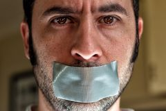 Close up portrait of a man with duct tape over his mouth Stock Images