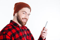 Close-up portrait of man with earphones holding mobile phone Royalty Free Stock Photo