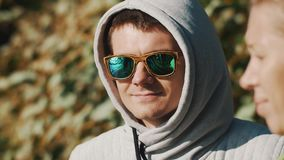Close up portrait of a man in hood and sunglasses smiles on summer windy day stock video