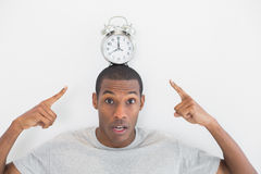 Close up portrait of a man pointing at alarm clock over his head Stock Image