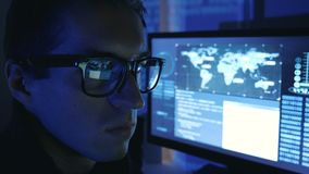 Close-up portrait of a Man Professional Geek Programmer in glasses working at computer in a data center filled with