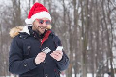 Portrait of young man with santa hat and sunglasses holding smartphone with credit card. royalty free stock photos