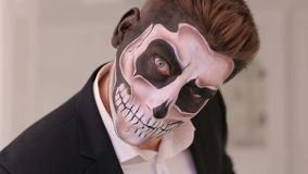 Close-up portrait of a man with a skull makeup. Dia de los muertos. Close-up portrait of a man with a skull makeup dressed in a tail-coat. Dia de los muertos stock video