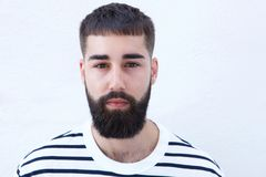 Close up man in striped shirt with beard staring. Close up portrait of man in striped shirt with beard staring Stock Photography