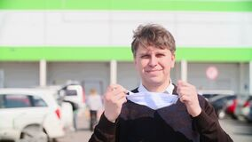 Close-up portrait of a man taking off a medical mask from his face against the background of a shopping center and car parking