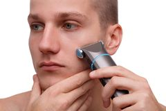 Close-up portrait of a man with a trimmer at the face isolated on a white background. Royalty Free Stock Photos