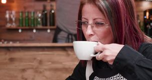 Close up portrait of mature businesswoman in her 40s typing on laptop. While drinking coffee in vintage and stylish coffee shop or restaurant stock footage