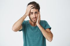 Close up portrait of mature caucasian bearded man in blue t-shirt, holding hand on forehead and cheek looking tired and. Bored after long day at work royalty free stock photos